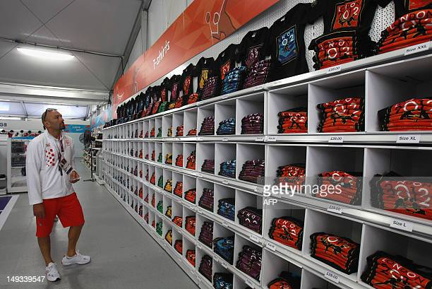 An athlete views merchandise at the Olympic Village ahead of the London 2012 Olympic Games at the Olympic Park on July 26, 2012 in London. AFP PHOTO...