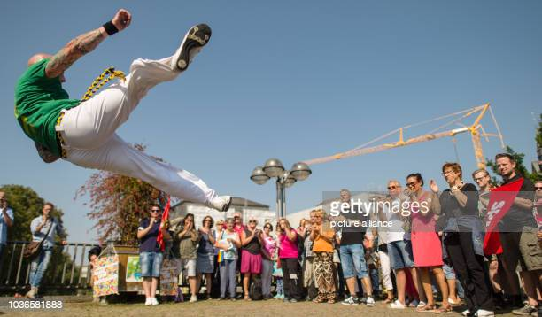 An athlete with the group Arte Negra performs a Capoeira jump at a counterdemonstration to the closing event for the Alternative for Germany 2016...