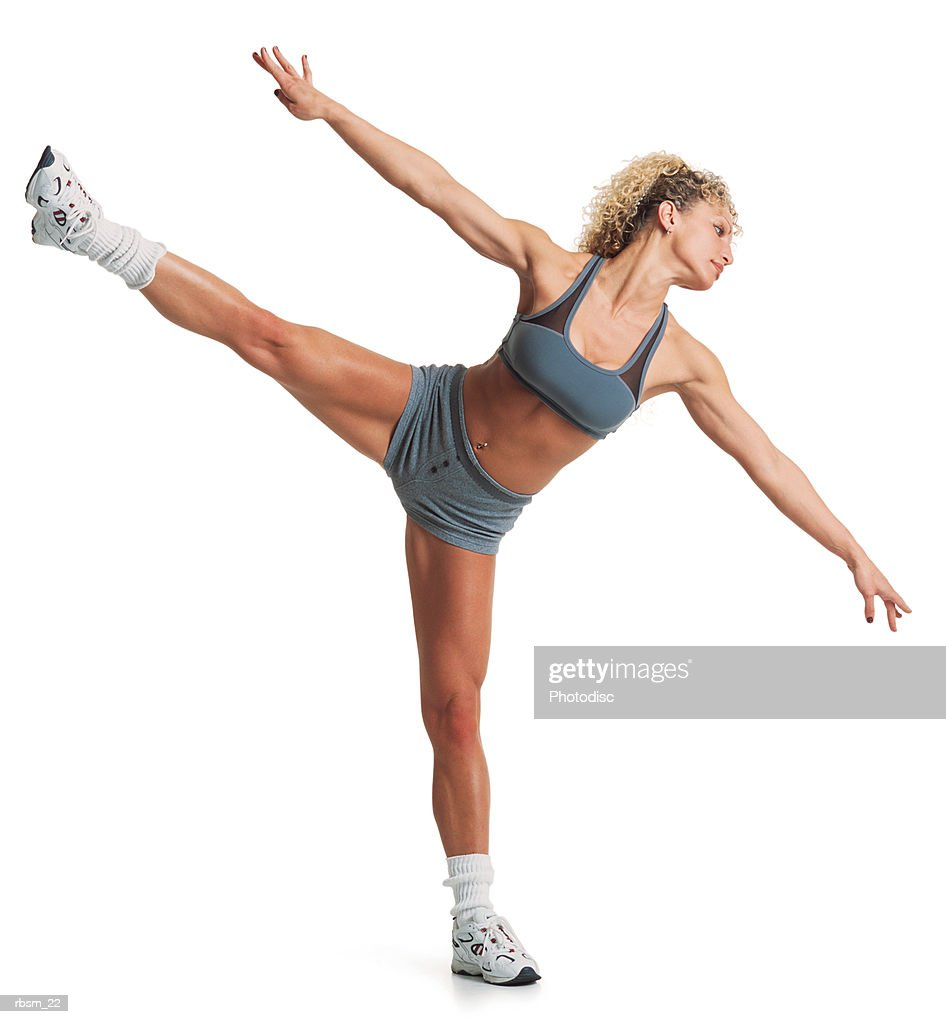 an athletic caucasian female in a grey workout outfit stretches out by balancing on one leg and extending her arms : Foto de stock