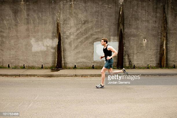 An athletic man jogging past a concrete wall in Portland, Oregon.