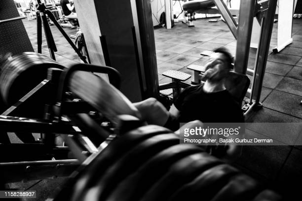 An athletic man making an effort while exercising on a leg press in a health club.