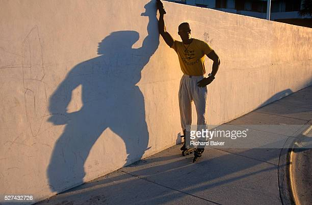 An athletic man poses against a wall on Ocean Drive in Miami Beach Florida This fine specimen of a man wears rollerblades and trousers tucked into...