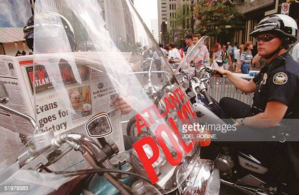 An Atlanta motorcycle police officer reads an Olympic news update in the local Atlanta JournalConstitution paper in downtown Atlanta Georgia 22 July...