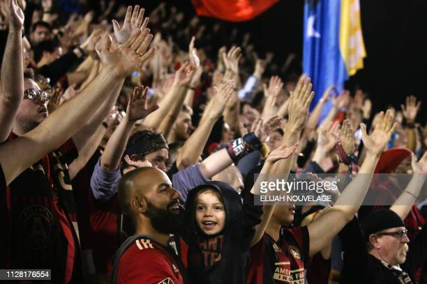 An Atlanta United fans raise their arms in the second half of the CONCACAF Champions League playoff football match between Atlanta United and...