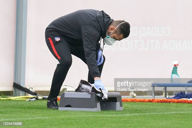 An Atletico de Madrid worker sprays sanitizing solution on the equipment during a training session at Estadio Cerro del Espino on May 12 2020 in...