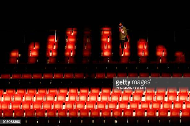 TOPSHOT An Atletico fan waits for the start of the Europa League Round of 32 second leg football match between Club Atletico de Madrid and FC...