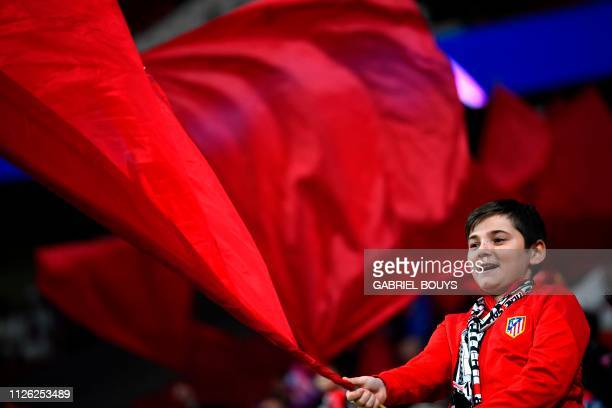 An Atletico Madrid fan cheers for his team before the UEFA Champions League round of 16 first leg football match between Club Atletico de Madrid and...