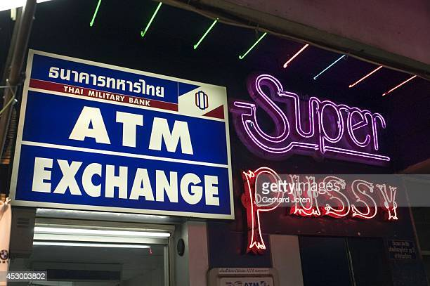 An ATM machine stands next to the entrance to a gogo bar called Super Pussy in the infamous red light district known as Patpong in central Bangkok