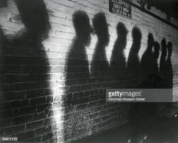 An atmospheric photo depicting shadows on a wall, Cincinnati, Ohio, 1930. The shadows belong to a group of men lined up for a bread line during the...