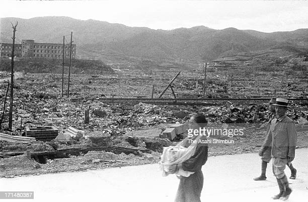 An atomic bomb surviver walks with holding bones of her parents who were killed by Nagasaki Atomic bomb in August 1945 in Nagasaki, Japan. The...