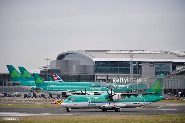 An ATR 72600 passenger aircraft operated by Aer Lingus Group Plc passes other Aer Lingus aircraft as it taxis on the tarmac at Dublin Airport...