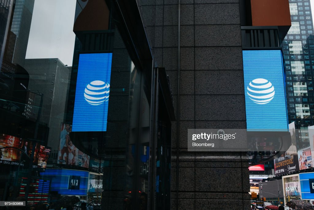 An AT&T Inc. logo is reflected in a store window in New York, U.S., on Wednesday, June 13, 2018. AT&T Inc.'s sweeping court victory allowing its takeover of Time Warner Inc. delivers a sharp setback to the Justice Department's new approach to policing mergers under President Donald Trump and promises to spark a merger wave across industries. Photographer: Christopher Lee/Bloomberg via Getty Images