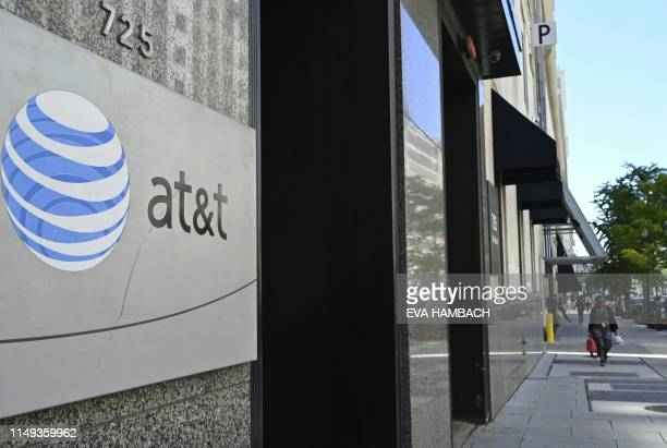 An AT&T telecommunication logo is seen at the entrance of a building in Washington, DC June 11, 2019.