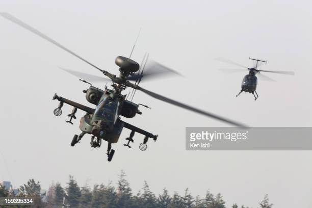 An attacking helicopter AH64D 'Apache' and OH6 'Cayuse' flly during the annual new year parachute exercise at Japan Ground SelfDefense Force...