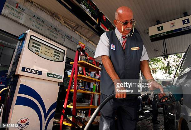 An attendant adds fuel to a car at a gas station in Mumbai India on Thursday Nov 29 2007 India's economy grew last quarter at the slowest pace since...