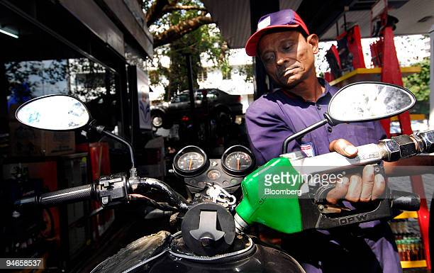 An attendant adds fuel to a motorbike at a gas station in Mumbai India on Thursday Nov 29 2007 India's economy grew last quarter at the slowest pace...