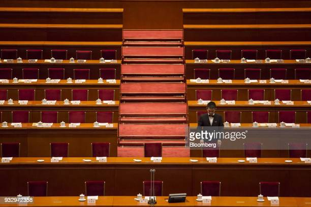 An attendant adjusts a chair ahead of a session during the first session of the 13th National People's Congress at the Great Hall of the People in...
