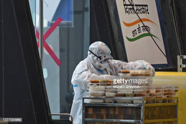 An attendant arranges food packets for patients outside a ward at the Commonwealth Games Village sports complex, temporarily converted into COVID-19...