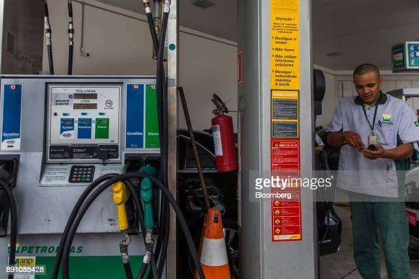 An attendant assists a customer at a Petrobras Distribuidora SA gas station in Sao Paulo Brazil on Monday Dec 11 2017 Petroleo Brasileiro SA  is...