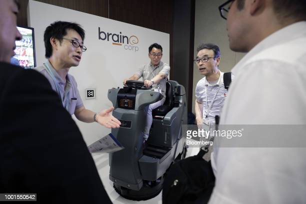 An attendant center sits on an International Cleaning Equipment RS26 rider auto scrubber powered by Brain Corp's Brain OS at the SoftBank World 2018...