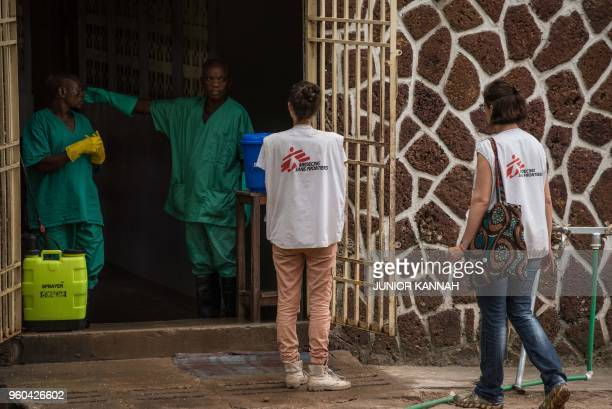 An attendant charged to handle the access to the Ebola security zone talks to Doctors Without Borders team members outside the Wangata Reference...