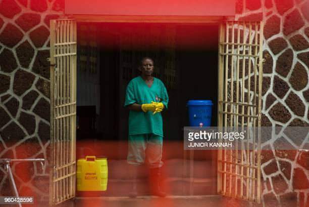 TOPSHOT An attendant charged to handle the access to the Ebola security zone stands at the entrance of the Wangata Reference Hospital in Mbandaka...