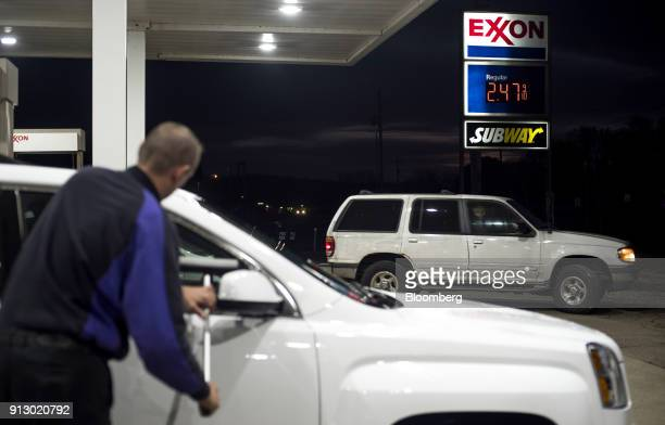 An attendant cleans the windows of a vehicle for a customer at an Exxon Mobil Corp gas station in Nashport Ohio US on Friday Jan 26 2018 Exxon Mobil...