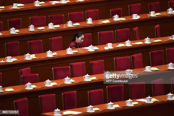 An attendant clears under tables used by Chinese leaders after the closing of the 19th Communist Party Congress at the Great Hall of the People in...