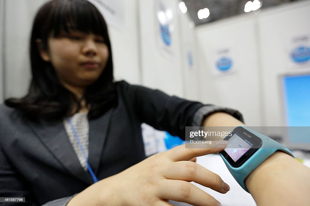 An attendant demonstrates A Biglobe Inc. internet connected device with a built-in sim card at the Wearable Expo in Tokyo, Japan, on Thursday, Jan. 15, 2015. The world largest expo for wearable devices and technologies will be held through Jan. 16. Photographer: Kiyoshi Ota/Bloomberg via Getty Images