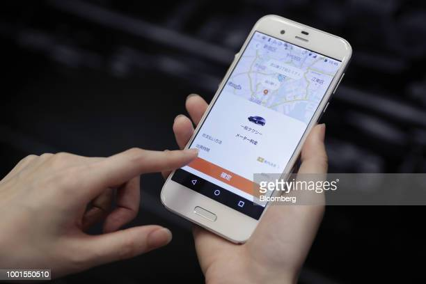 An attendant demonstrates the Didi Chuxing taxihailing application on a smartphone for a photograph at the SoftBank World 2018 event in Tokyo Japan...