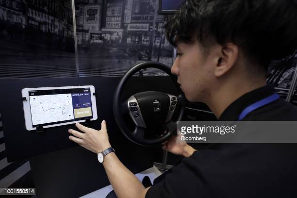 An attendant demonstrates the Didi Chuxing taxihailing application on a tablet device for a photograph at the SoftBank World 2018 event in Tokyo...