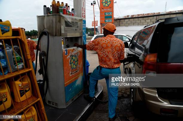 An attendant dispenses fuel into a vehicle's tank at a fuel station in the Maryland district of Lagos, on September 8, 2020. - The Nigerian...