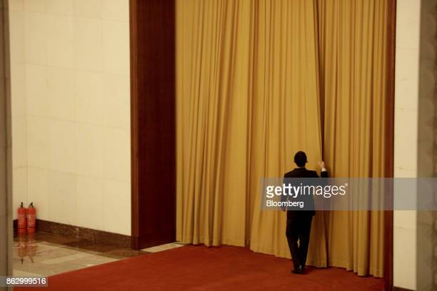 An attendant draws a curtain inside the Great Hall of the People during the 19th National Congress of the Communist Party of China in Beijing, China,...