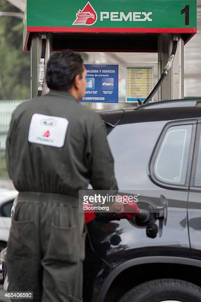 An attendant fills a customer's tank at a Petroleos Mexicanos gas station in Mexico City Mexico on Friday March 6 2015 Oil contracts worth more than...