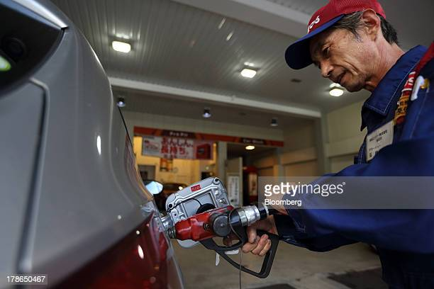 An attendant fills the tank of a vehicle at a gas station in Tokyo Japan on Friday Aug 30 2013 Japan's consumer prices increased at the fastest pace...