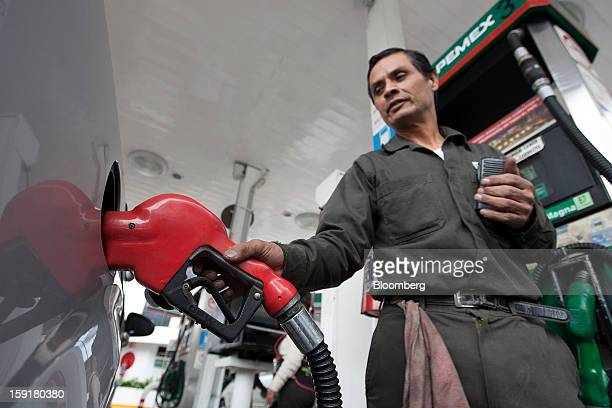 An attendant fills the tank of a vehicle with gasoline at a Pemex station in Mexico City Mexico on Tuesday Jan 8 2013 Mexico's government is speeding...