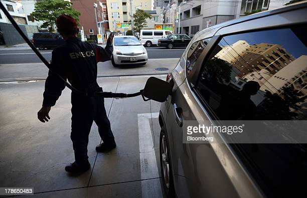 An attendant gestures towards a vehicle as another vehicle is refueled at a gas station in Tokyo Japan on Friday Aug 30 2013 Japan's consumer prices...