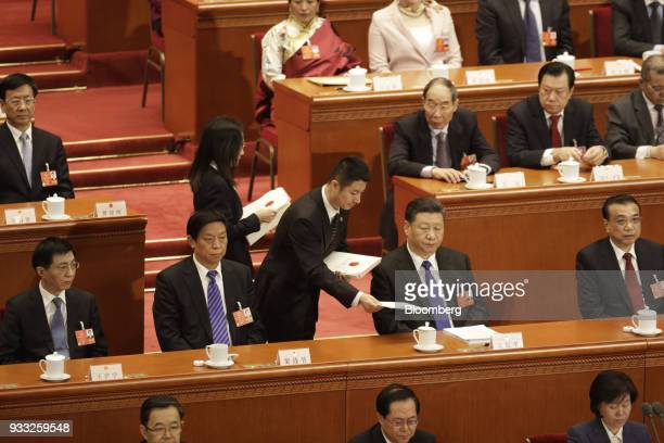 An attendant hands Xi Jinping China's president second row second right his ballots as Wang Huning member of the Communist Party of China's Politburo...
