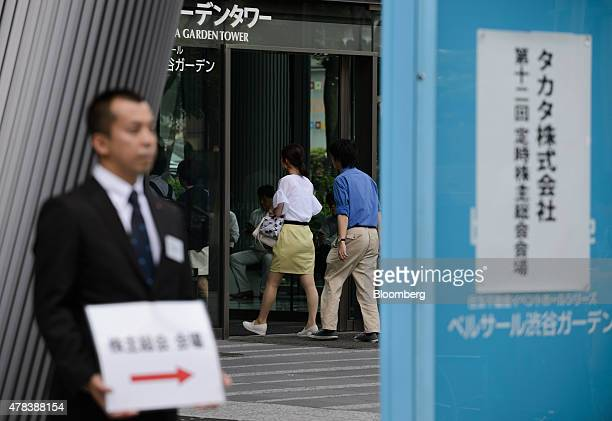 An attendant holds a sign for the Takata Corp annual general meeting as people enter to the venue in Tokyo Japan on Thursday June 25 2015 Fiat...