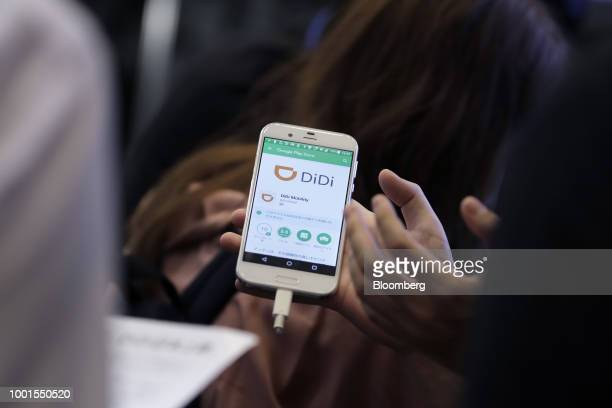 An attendant holds a smartphone displaying the Didi Chuxing logo while explaining about the company's taxihailing application to an attendee at the...