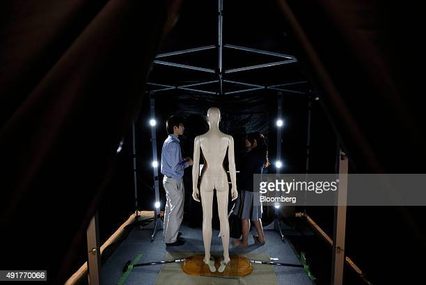 An attendant left speaks with an attendee inside the 3D body scanning booth at the CuttingEdge IT Electronics Comprehensive Exhibition at Makuhari...