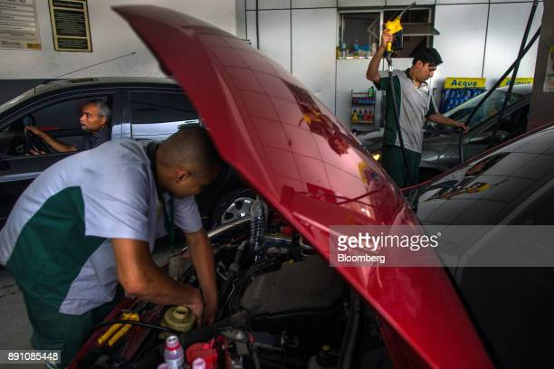 An attendant looks under the hood of a vehicle at a Petrobras Distribuidora SA gas station in Sao Paulo Brazil on Monday Dec 11 2017 Petroleo...