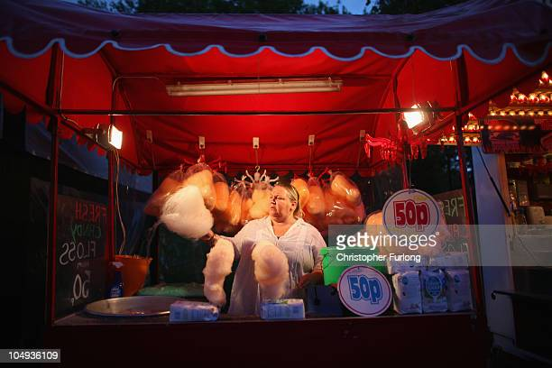 An attendant makes candy floss for revellers as they enjoy the thrills and fun of the traditional fair ground at the annual Goose Fair on October 6...