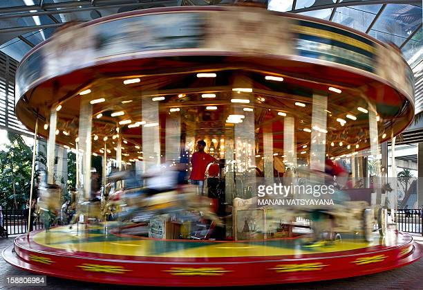 An attendant mans a carousel ride near Tumbalong Park in Sydney's Darling Harbour area on December 30 2012 Darling Harbour a bustling port and goods...