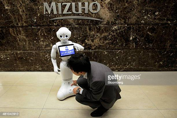 An attendant moves SoftBank Corp's humanoid robot Pepper at a Mizuho Bank Ltd branch in Tokyo Japan on Friday July 17 2015 Mizuho introduced Pepper...
