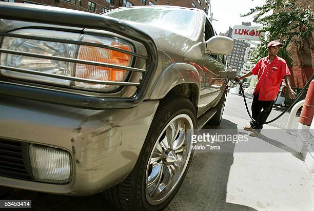 An attendant named Kumara fills the tank of a sport utility vehicle for a customer at a Lukoil gas station in the Chelsea neighborhood August 23 2005...