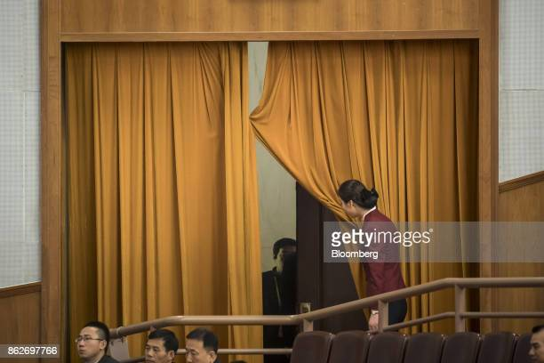 An attendant opens a curtain during the opening of the 19th National Congress of the Communist Party of China at the Great Hall of the People in...