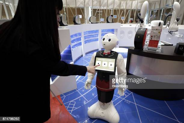 An attendant orders a cup of coffee by touching a screen on a SoftBank Group Corp Pepper humanoid robot during a media preview of the humanless cafe...