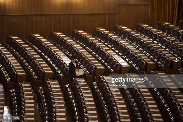 An attendant prepares ahead of a session during the first session of the 13th National People's Congress at the Great Hall of the People in Beijing...