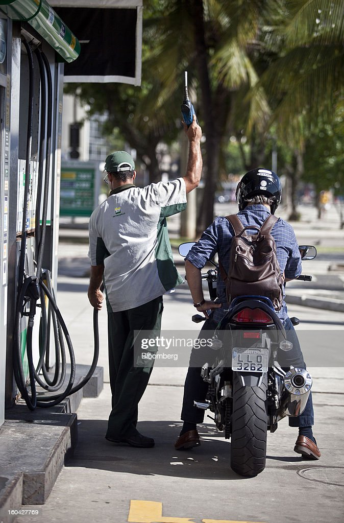 An attendant prepares to fill the tank of a motorcycle at a Petroleo Brasileiro SA (Petrobras) station in Rio de Janeiro, Brazil, on Thursday, Jan. 31, 2013. State-controlled oil company Petrobras announced earlier this week that it would raise gasoline and diesel prices by 6.6 percent and 5.4 percent, respectively. Photographer: Dado Galdieri/Bloomberg via Getty Images
